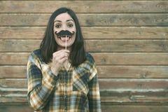 De grappige jonge snor van de vrouwenholding op stok stock foto