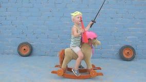 De grappige jongen blond in superheromasker zit op stuk speelgoed hobbelpaard het kind wordt bewapend met zwaard en signaalhoorn  stock videobeelden