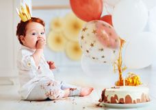 De grappige jongen die van de zuigelingsbaby zijn 1st verjaardagscake proeven Stock Foto's