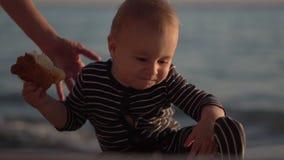 De grappige jongen met broodje op van hem dient langzame motie op het strand in stock video
