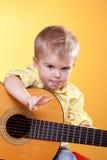De grappige jongen met gitaar toont vredesteken en tong Royalty-vrije Stock Fotografie