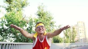 De grappige kerel buitenissige liften zijn handen omhoog zoals een winnaar stock footage