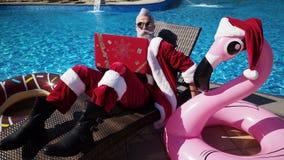 De grappige Kerstman die laptop met behulp van zit bij chaise en het gekscheren stock footage