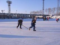 De grappige kinderen bij de piste in de winter schaatsen speelhockey royalty-vrije stock afbeelding