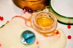 De grappige kleurrijke abstracte achtergrond met schoonheidsmiddelen roomt, transparante blauwe glasbal en gouden lotion af Stock Foto's