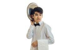De grappige knappe kelner kijkt weg en houdt het schoteldienblad dichtbij zijn die hoofd op witte achtergrond wordt geïsoleerd Stock Fotografie