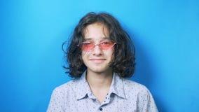 De grappige krullend-haired tiener in roze glazen onderzoekt de camera en toont o.k. teken, op blauwe achtergrond stock videobeelden