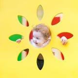 De grappige krullende babymeisje het spelen huid - en - zoekt Stock Afbeeldingen