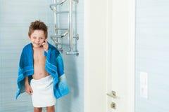 De grappige leuke kleine jongen knipoogt zich bevindt in de badkamers met een handdoek op zijn schouders royalty-vrije stock foto