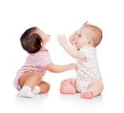 De grappige meisjes die van babyskinderen samen spelen stock afbeelding