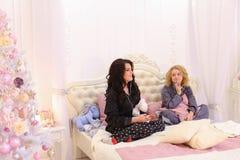 De grappige meisjes komen weg aan het meest volledig op bed voor koele muziek op smartph Royalty-vrije Stock Foto's