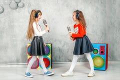 De grappige meisjes zingen en luisteren aan muziek in hoofdtelefoons Het bureau van C Stock Foto's