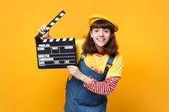 De grappige meisjestiener die in Franse baret, de klassieke zwarte film van de denim sundress holding clapperboard isoleerde op g stock foto
