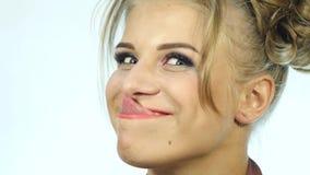 De grappige mooie vrouw toont tong en aanrakingen het uiteinde van de neus 4K stock videobeelden