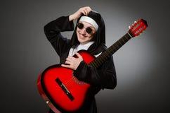 De grappige non met het rode gitaar spelen Stock Foto