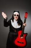 De grappige non met het rode gitaar spelen Royalty-vrije Stock Foto
