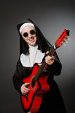 De grappige non met het rode gitaar spelen Stock Fotografie