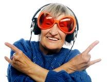 De grappige oude dame het luisteren muziek en het tonen beduimelt omhoog royalty-vrije stock afbeeldingen
