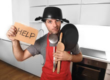 De grappige pan van de mensenholding met pot op hoofd in schort bij keuken die om hulp vragen Royalty-vrije Stock Afbeelding
