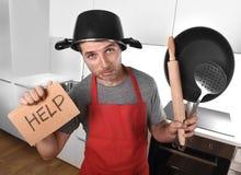 De grappige pan van de mensenholding met pot op hoofd in schort bij keuken die om hulp vragen Royalty-vrije Stock Afbeeldingen