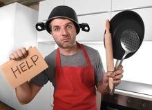 De grappige pan van de mensenholding met pot op hoofd in schort bij keuken die om hulp vragen Stock Foto's