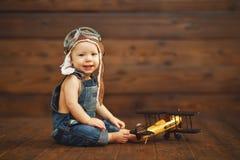 De grappige proefvliegenier van de babyjongen met vliegtuig het lachen royalty-vrije stock foto's