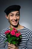 De grappige romantische holding van de zeemansmens nam bloemen toe Royalty-vrije Stock Foto's