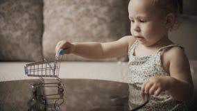 De grappige spelen van het babymeisje met stuk speelgoed boodschappenwagentje stock footage