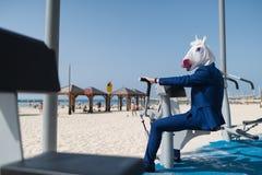 De grappige sportman in elegant kostuum en komisch masker doet oefeningen royalty-vrije stock fotografie