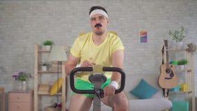 De grappige sportman van de jaren '80 met een snor is thuis bezet op een hometrainer en drinkt water stock footage