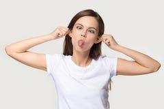 De grappige tiener maakt aapgezicht het loensen ogen die tong tonen stock fotografie