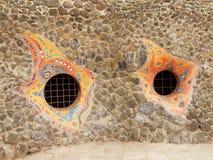 De grappige vensters voerden met kleine stenen in mozaïek, duisternis achter de tralies in de venstermuur bulit van gebroken sten Stock Afbeeldingen