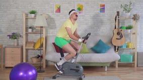 De grappige vermoeide atleet van de jaren '80 met een snor is bezig geweest op een hometrainer met huis langzame mo stock videobeelden