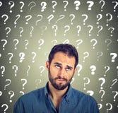 De grappige verwarde sceptische mens die het kijken denken omhoog heeft vele vragen stock fotografie