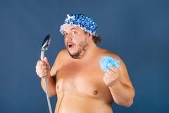 De grappige vette mens in blauw GLB zingt in de douche stock fotografie