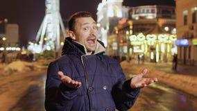 De grappige volwassen mens verschijnt voor camera bij de vage stadsachtergrond stock footage