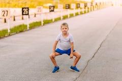 De grappige zeven-jaar-oude jongen in blauwe borrels en tennisschoenen is op de bestrating in de zomer royalty-vrije stock fotografie