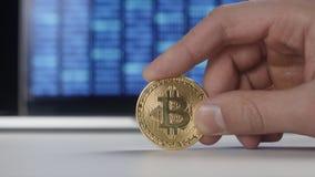 De greep gouden Bitcoin BTC van mensenhanden op binaire codeachtergrond mijnbouw en handel stock footage