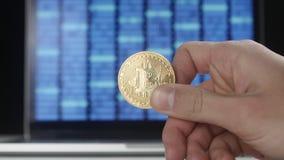 De greep gouden Bitcoin BTC van mensenhanden op binaire codeachtergrond mijnbouw en handel stock video