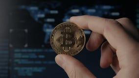 De greep gouden Bitcoin van mensenhanden op binaire codeachtergrond mijnbouw en handel stock videobeelden