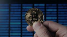 De greep gouden Bitcoin van mensenhanden op binaire codeachtergrond mijnbouw en handel stock video