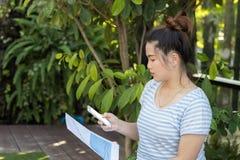 De greep slim telefoon van de close-up mooi Aziatisch vrouw en lijstdocument Stock Afbeeldingen