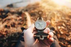 De greep uitstekend kompas van de Hipsterreiziger ter beschikking op achtergrond van hem benen in wandelingslaarzen royalty-vrije stock foto's