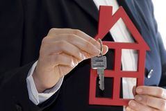 De greep van de hand een sleutel en een huis Royalty-vrije Stock Foto