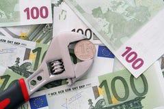 De greep van het één roebelmuntstuk in een regelbare moersleutel op euro bankbiljetten Stock Fotografie