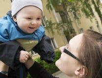 De greepbaby van de moeder op handen Mammaspel met baby De baby glimlacht a stock afbeelding