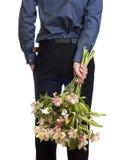 De greepboeket van de mens van bloemen achter zijn rug. stock afbeelding