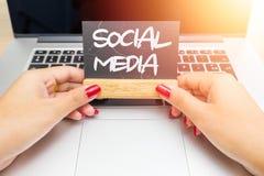 De greepbord van vrouwenhanden met Sociale media die, laptop op achtergrond van letters voorzien royalty-vrije stock afbeelding