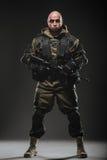 De greepmachinegeweer van de militairmens op een donkere achtergrond stock afbeeldingen