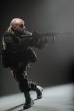 De greepmachinegeweer van de militairmens op een donkere achtergrond stock fotografie